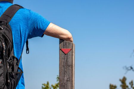 Close-up of a hiker resting his arm on a wooden pole with a red trail marker on