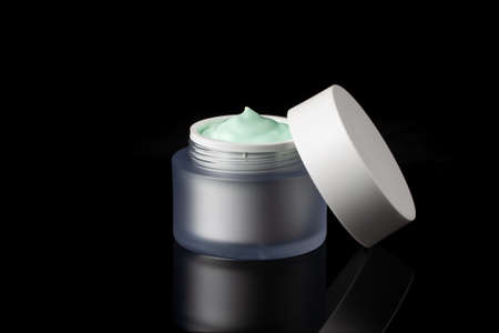 Glass jar of beauty face cream with cap. Isolated on black background