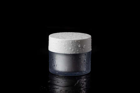 A wet glass jar of beauty face cream with cap. Isolated on black background Stok Fotoğraf