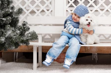 겨울 화창한 날에 집 밖에 벤치에 흰색 강아지와 어린 소녀