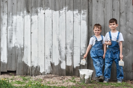 Boys-painters with brushes and paint at an old wall on a summer day photo