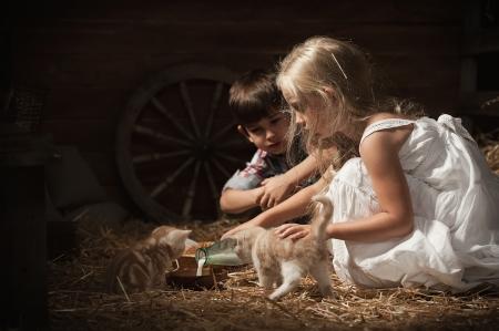 소년과 소녀 젊은 새끼 고양이 소박한 헛간에 우유를 먹이