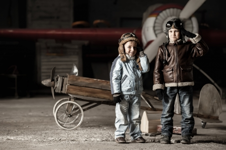 Young aviators in homemade aircraft in a large hangar Banco de Imagens