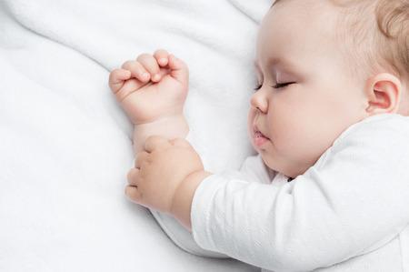 durmiendo: Despreocupado dormir pequeño bebé en una cama