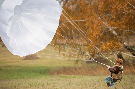Little girl running with a parachute on the field in sunny autumn day Stock Photo