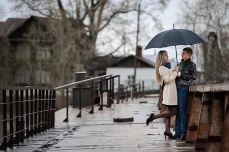 love in rain: Guy and the girl under an umbrella on a bridge on a cloudy rainy day
