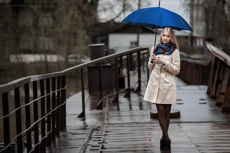 비에서 다리에 우산 어린 소녀
