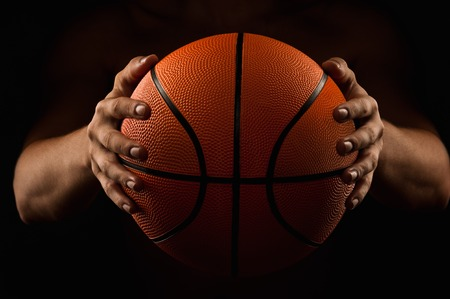 Basketball in the hands of the man close up on a black background Stock Photo