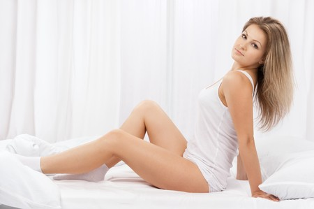 The young beautiful woman in bed on white photo