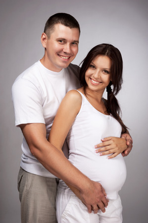 Happy pregnant woman with the husband in studio on grey