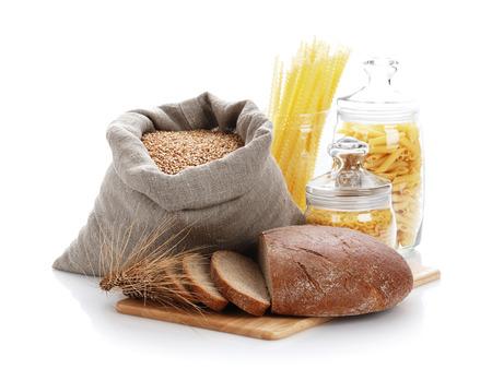 bolsa de pan: Cortar el pan, bolso con trigo y macarrones en el recipiente de vidrio sobre un fondo blanco