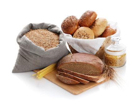 canasta de pan: Montón del vario pan, bolso con trigo y macarrones en un fondo blanco