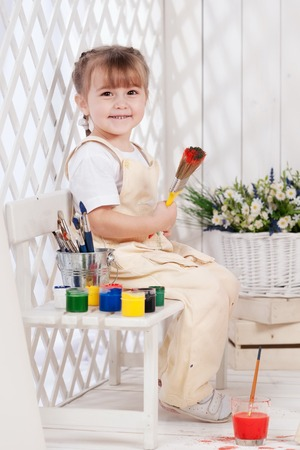 Little girl artist paints in studio photo