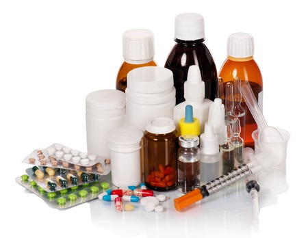 Different medical bottles and tablets isolated on white photo