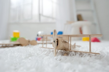small room: Wooden airplane toy in the childrens room on the carpet Stock Photo