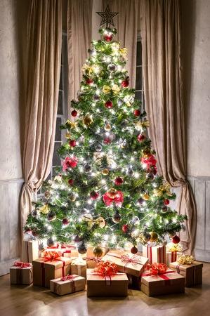 밤에 창문 화려한 조명 화환 및 선물 크리스마스 트리
