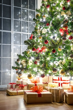 Christmas tree with colorful lights garlands and gifts at the window at night