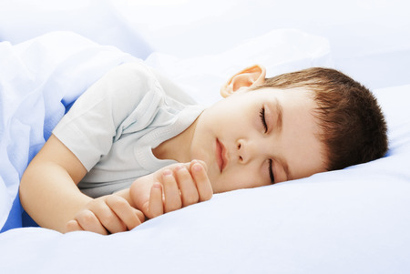 Carefree sleeping little boy on a bed