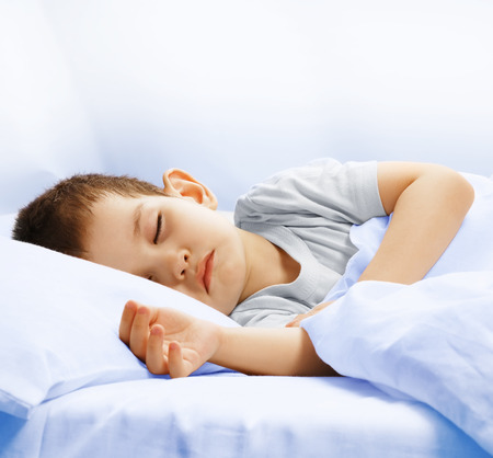 oversleep: Carefree sleeping little boy on a bed
