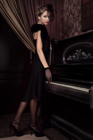 Portrait of a young girl in a retro style in the interior of the piano photo