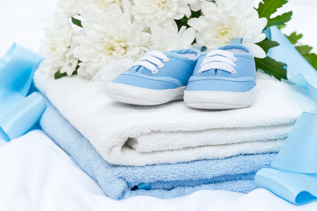 Booties and a towel after a shower for a baby Imagens