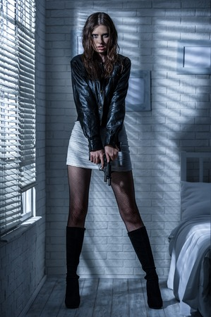 Boos meisje herladen van het pistool in een donkere kamer
