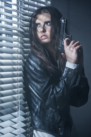 Angry girl reload the gun in a dark room photo