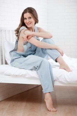 overol: Retrato de la joven en la cama en blanco