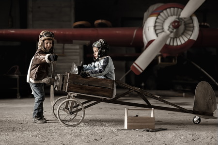 Young Aviators in a homemade aircraft in a hangar with these planes
