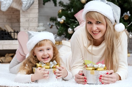 Happy mother with her daughter by the fireplace under the Christmas tree photo