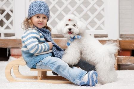 겨울 화창한 날에 작은 흰색 개 썰매에 어린 소녀