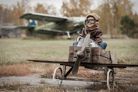 Young boy-pilot in the plane at the airport handmade autumn Banco de Imagens