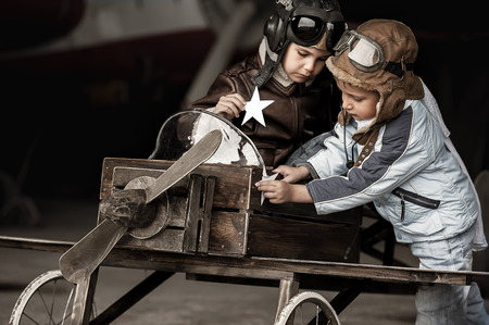 Young aviators in homemade aircraft in a large hangar Imagens