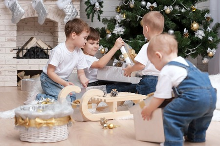Children make out gifts at Christmas tree photo