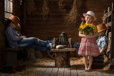 barefoot cowboy: Three young children playing cowboys in the barn Stock Photo