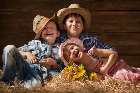 격납고에서 건초에 세 아이들이 웃고
