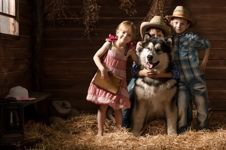 big family: Three small children with a dog in the barn on straw
