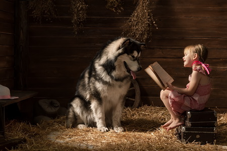 Little girl reading a book to his dog in the barn Imagens