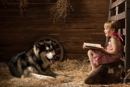 Little girl reading a book to her dog in the barn photo