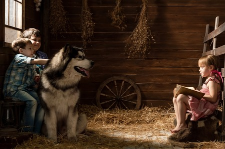 Girl reads the book to his brothers and a dog in a stable photo