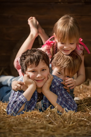 barefoot cowboy: Three laughing children on hay in a hangar