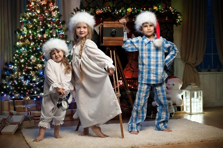 Young children are photographed near the Christmas tree