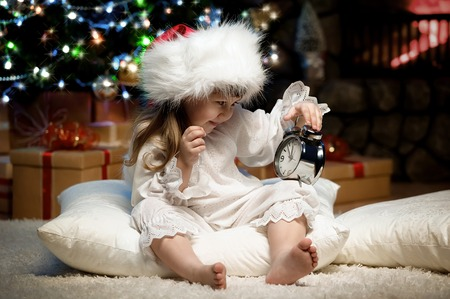 Little girl with an alarm clock on a pillow under the Christmas tree in the fireplace waiting for Santa Claus