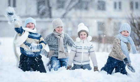 冬の澄んだ日で雪の中で遊んでいる子供のグループ
