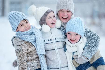 Group of kids playing in the snow in winter clear day Banco de Imagens