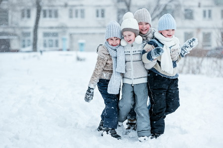 Group of kids playing in the snow in winter clear day Stock Photo