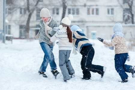 Group of kids playing in the snow in winter clear day Imagens