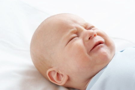 The crying small child on the bed