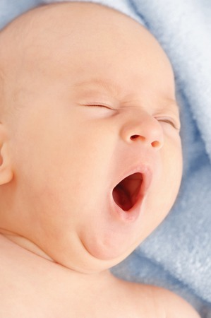 The small child yawns after bathing on the bath towel photo