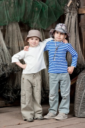 Two little boys of the fisherman with fishing tackles in a barn photo